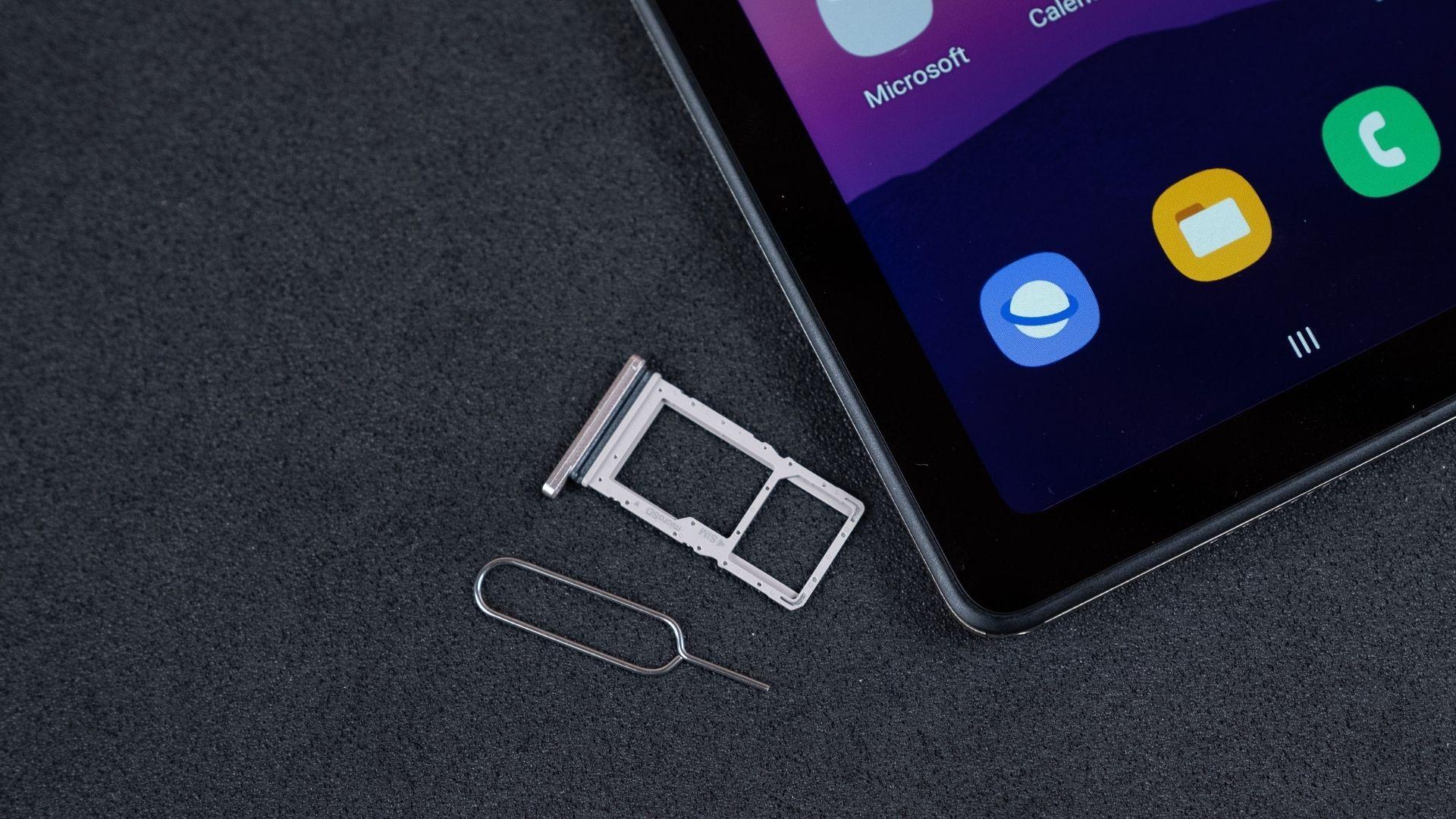 Parte do Galaxy Tab A7 em um fundo cinza com a gaveta do chip e a chave para abrir o compartimento