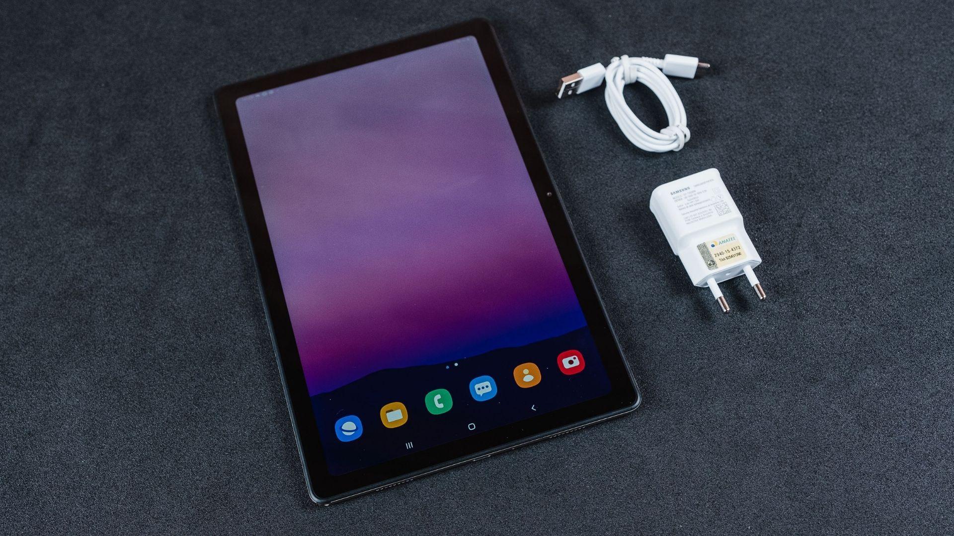 Galaxy Tab A7 com tela acesa em fundo cinza, ao lado do cabo e adaptador de tomada