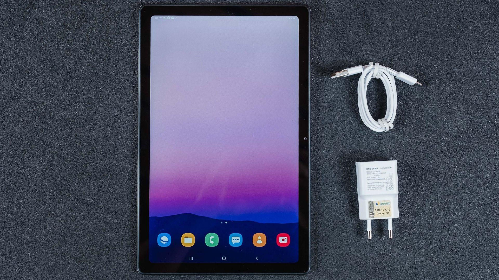 Galaxy Tab A7 em um fundo cinza com o carregador e cabo USB ao lado