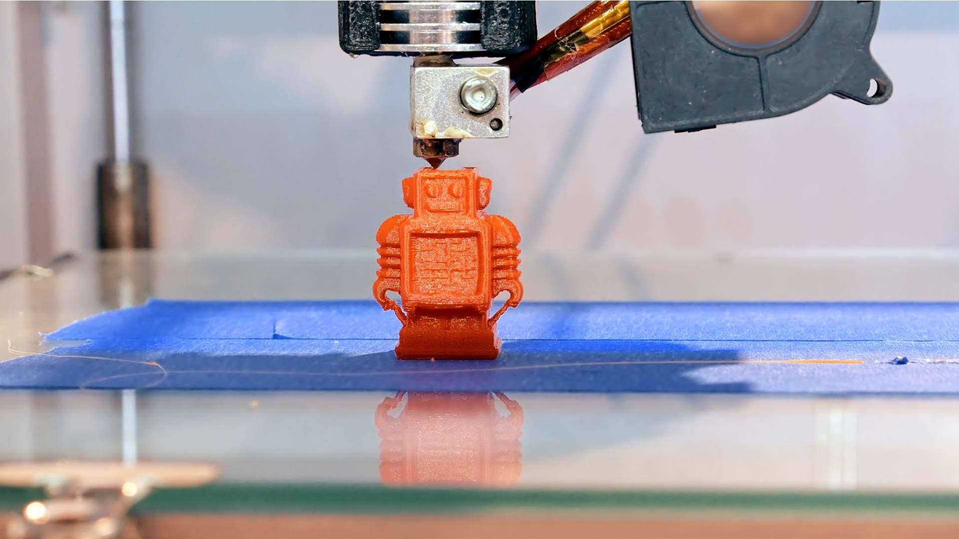 Robô de brinquedo laranja sendo construído por impressora 3D