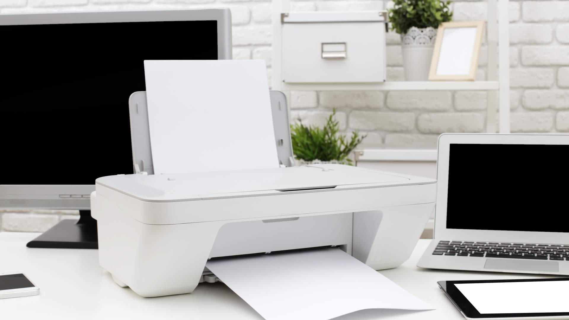 Mesa de escritório com impressora branca ao centro, acompanhada de notebook, tablet e monitor ao redor