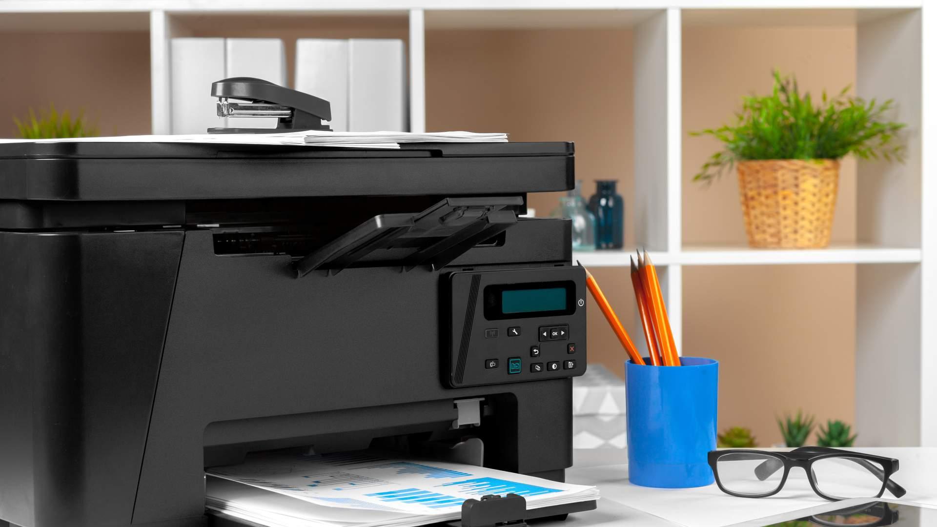 Impressora grande e preta à esquerda da tela, sobre mesa de escritório com óculos e copo com diversos lápis em volta