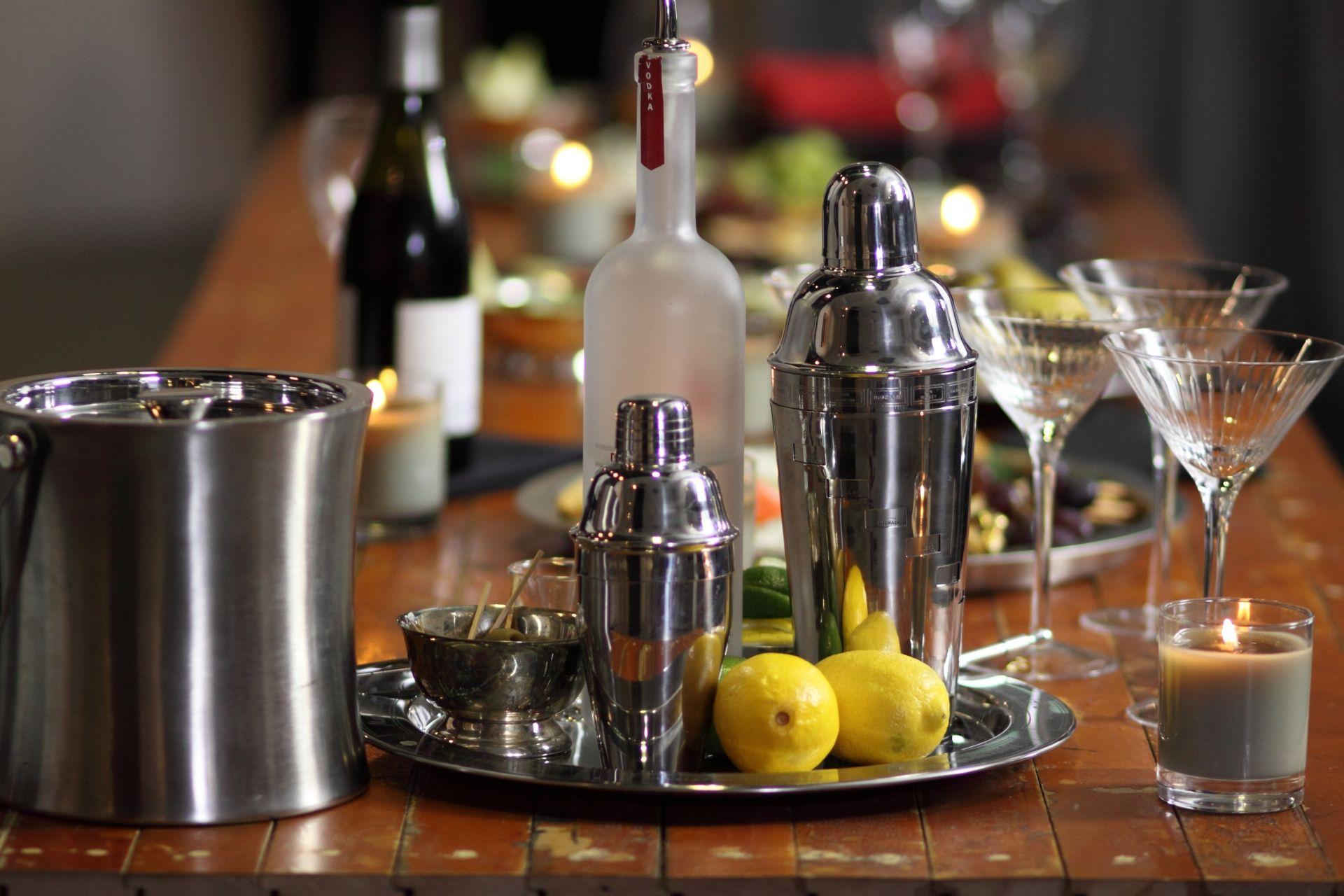Mesa de madeira com coqueteleiras em cima de uma bandeja prata junto com um balde de gelo e três taças de martini