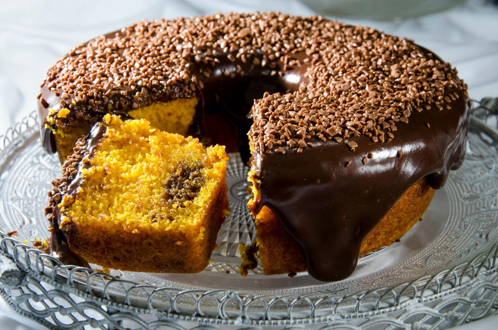 Bolo de cenoura com calda de chocolate e granulados por cima e fatia cortada