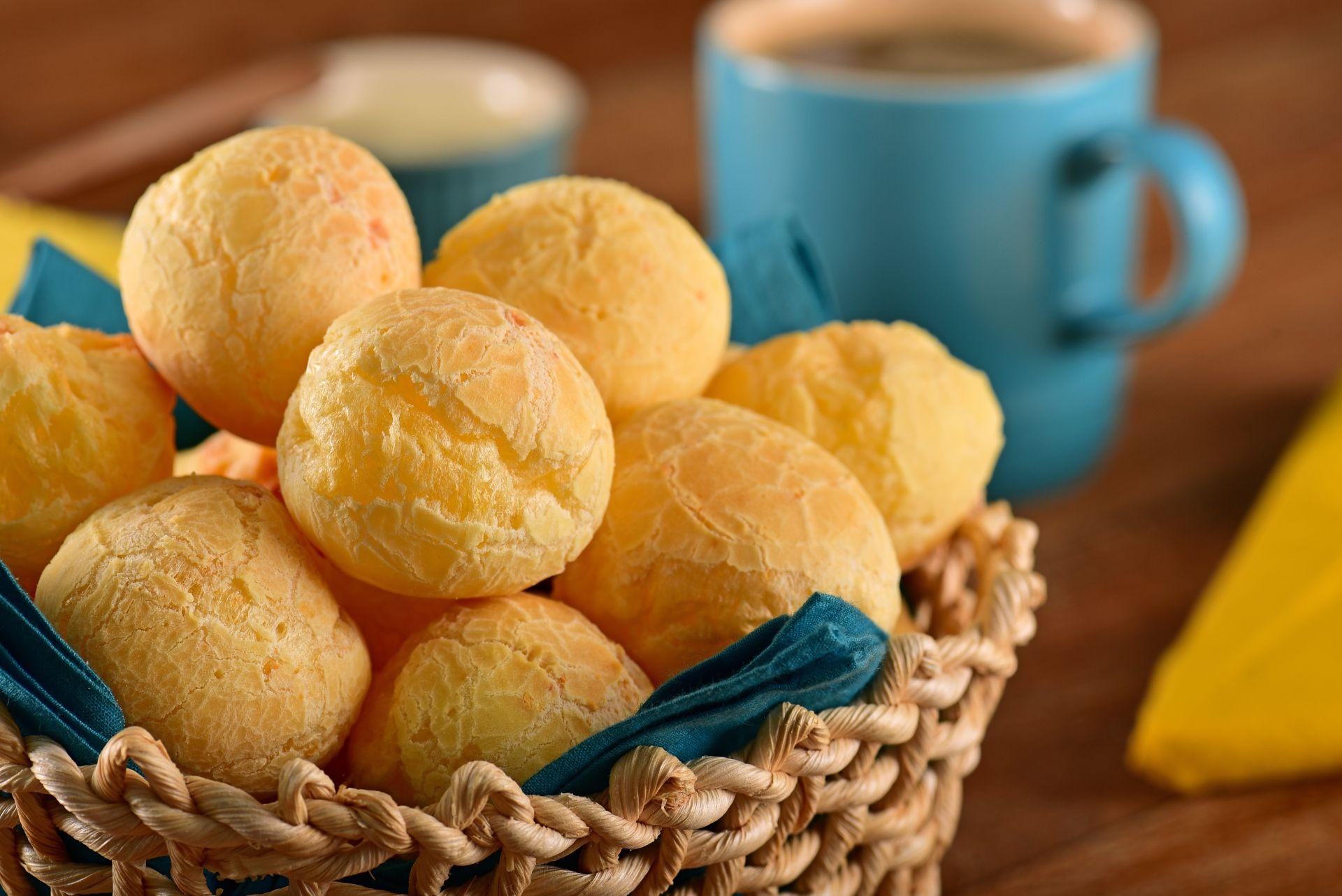Cesto de vime com pães de queijo na frente de uma caneca de café