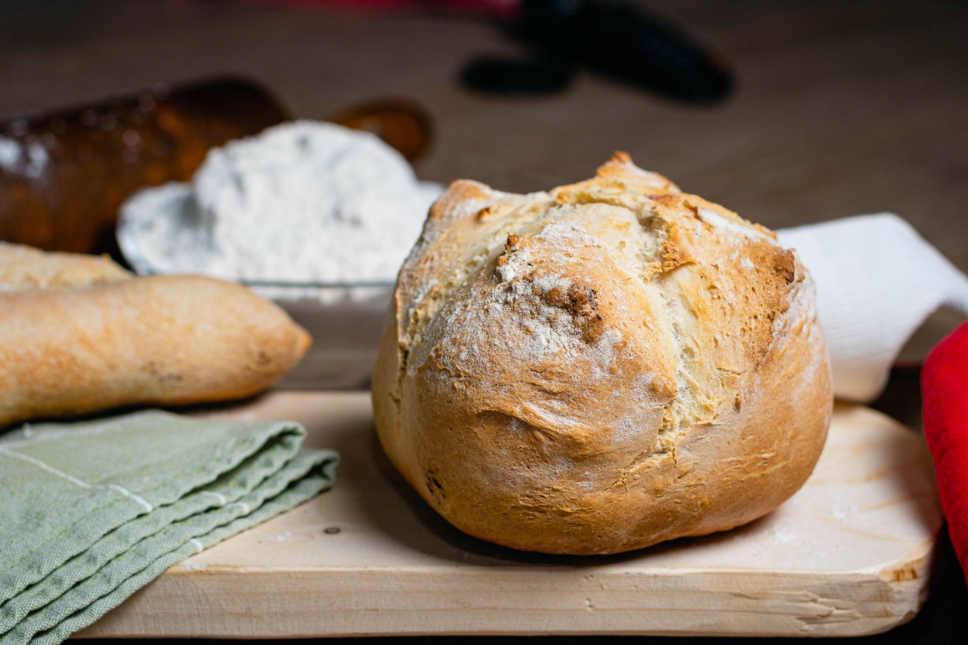 Pão caseiro redondo numa tábua com ingredientes na frente de um recipiente com farinha de trigo