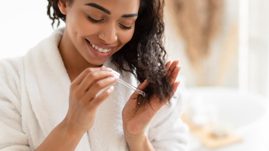 Mulher de roupão branco sorrindo enquanto aplica óleo para cabelo nos fios