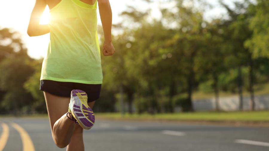 Mulher usando tênis da Olympikus enquanto corre em um parque