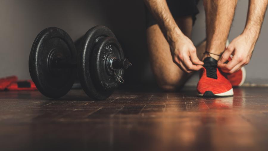 Homem amarrando tênis para academia antes do treino com um peso ao lado