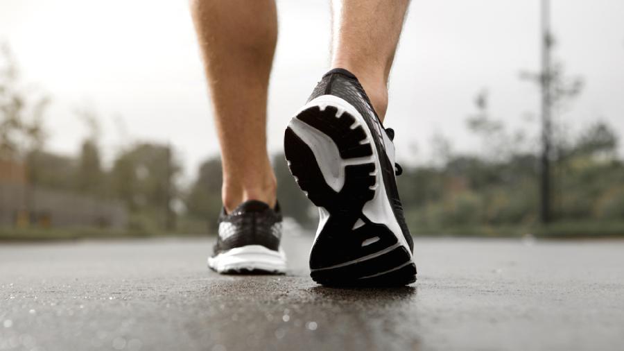 Homem usando tênis para caminhada com solado preto e branco enquanto caminha no asfalto