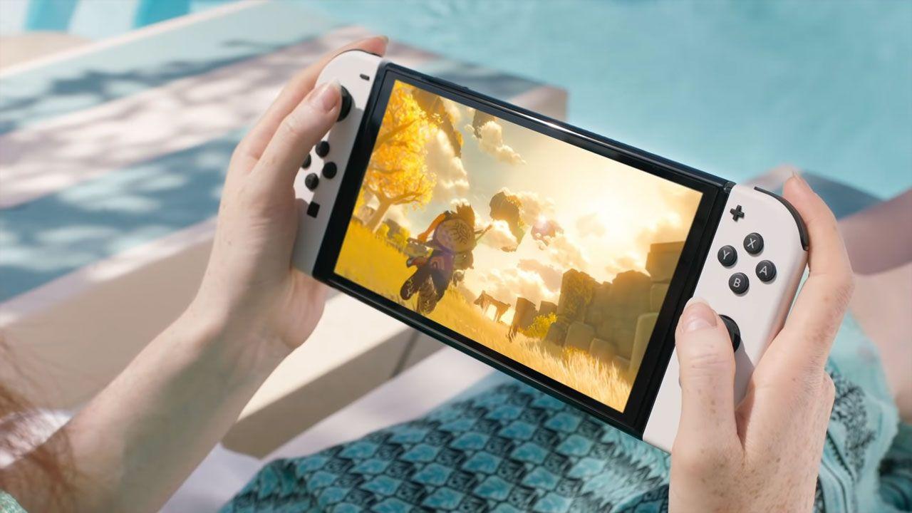 Nintendo Switch OLED em mãos, com jogo na tela.