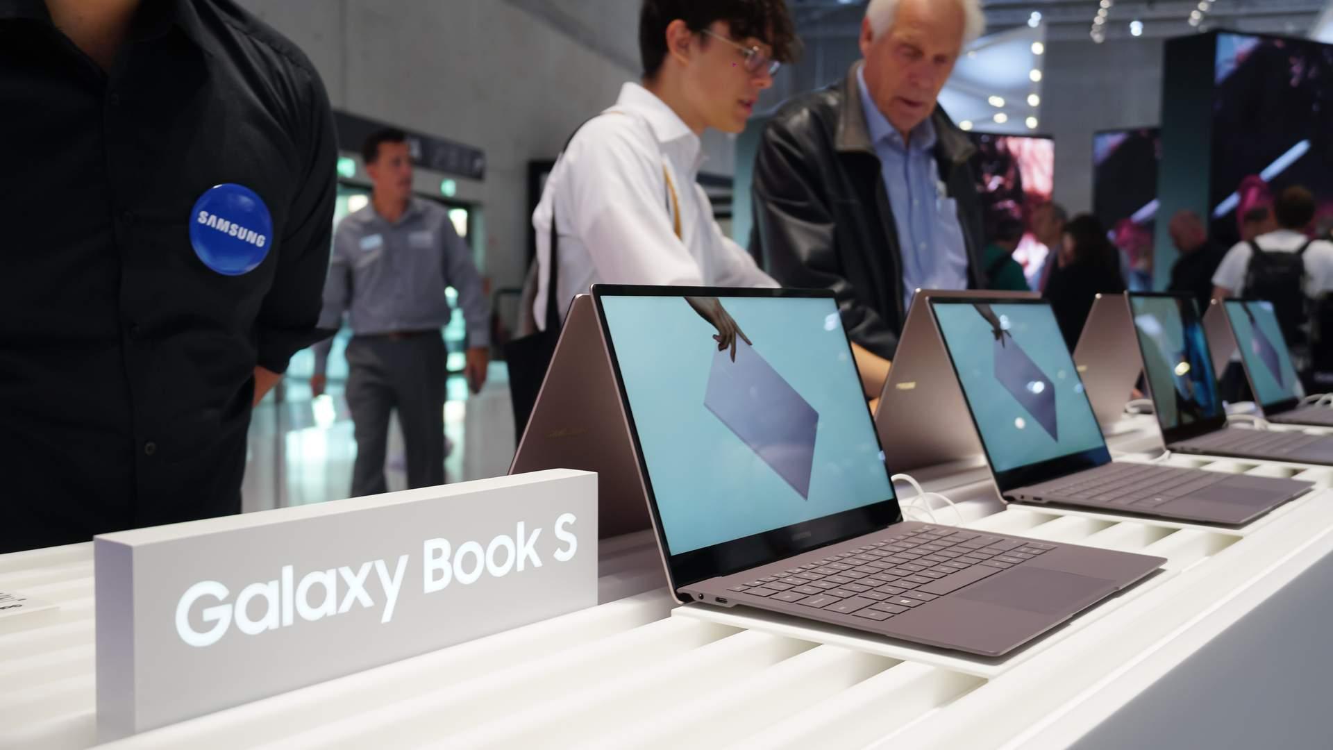 Notebooks Samsung Galaxy Book S abertos e enfileirados sob mesa branca, com homens olhando para ele