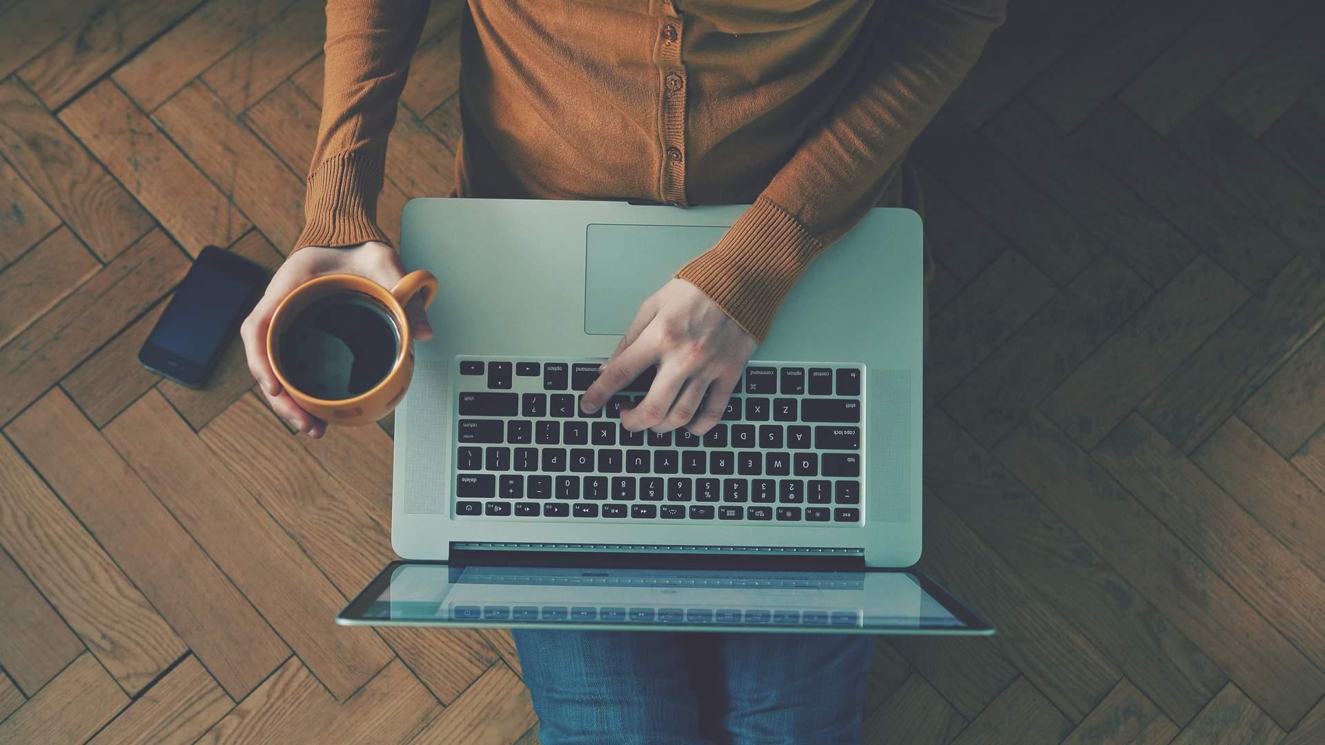 Pessoa sentada no chão usando notebook no colo e segurando caneca de café na mão esquerda