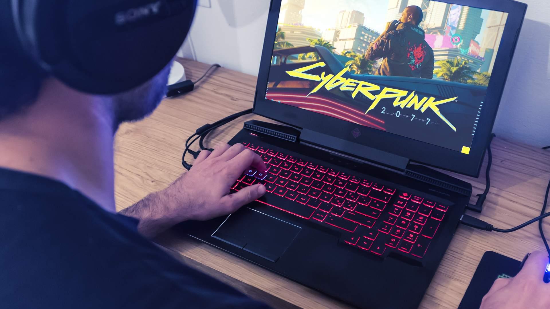 Homem jogando o game Cyberpunk 2077 em notebook preto com teclas vermelhas
