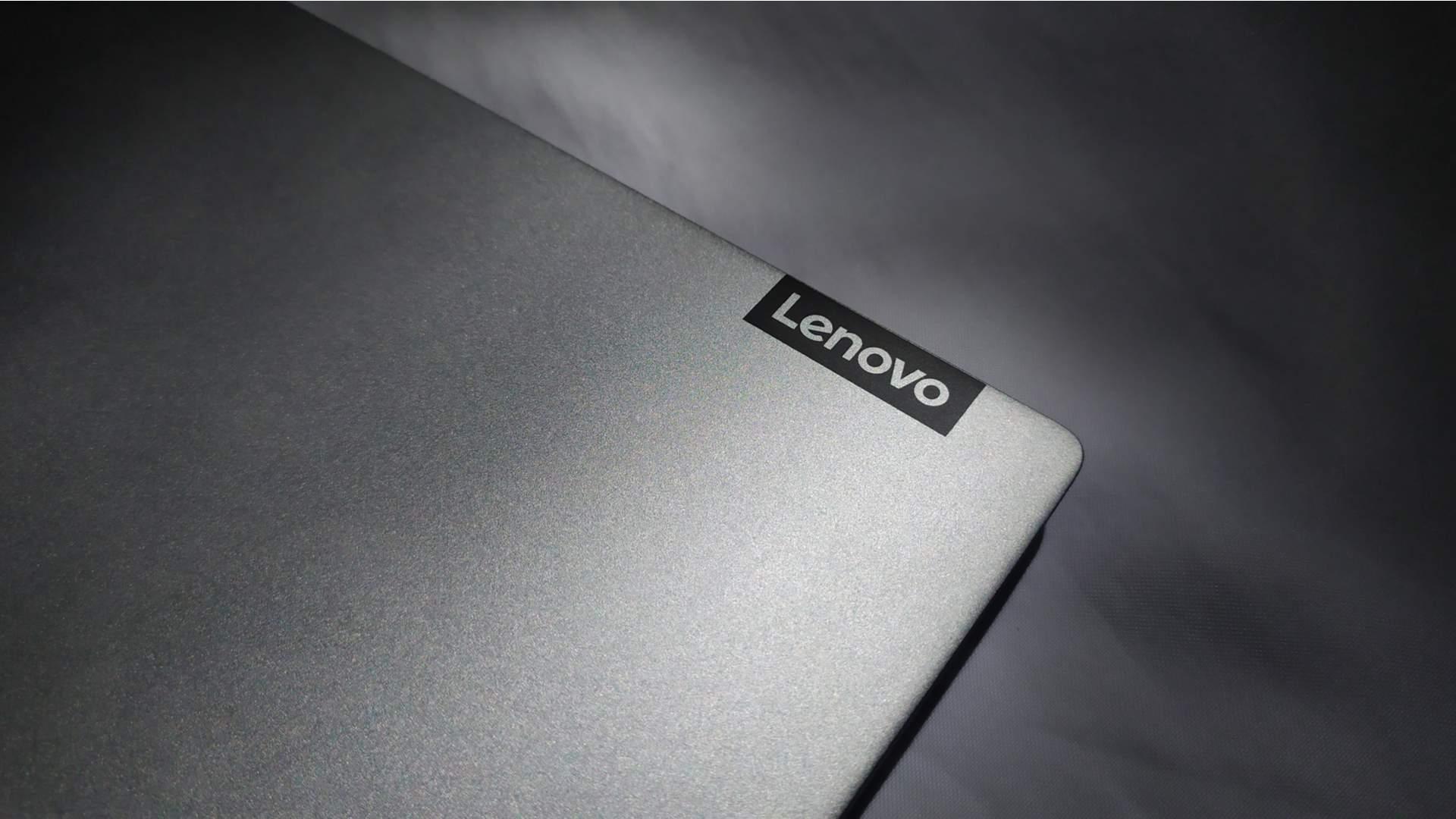 Pedaço da ponta do notebook Lenovo cinza, com pequena etiqueta com a marca Lenovo na lateral dele
