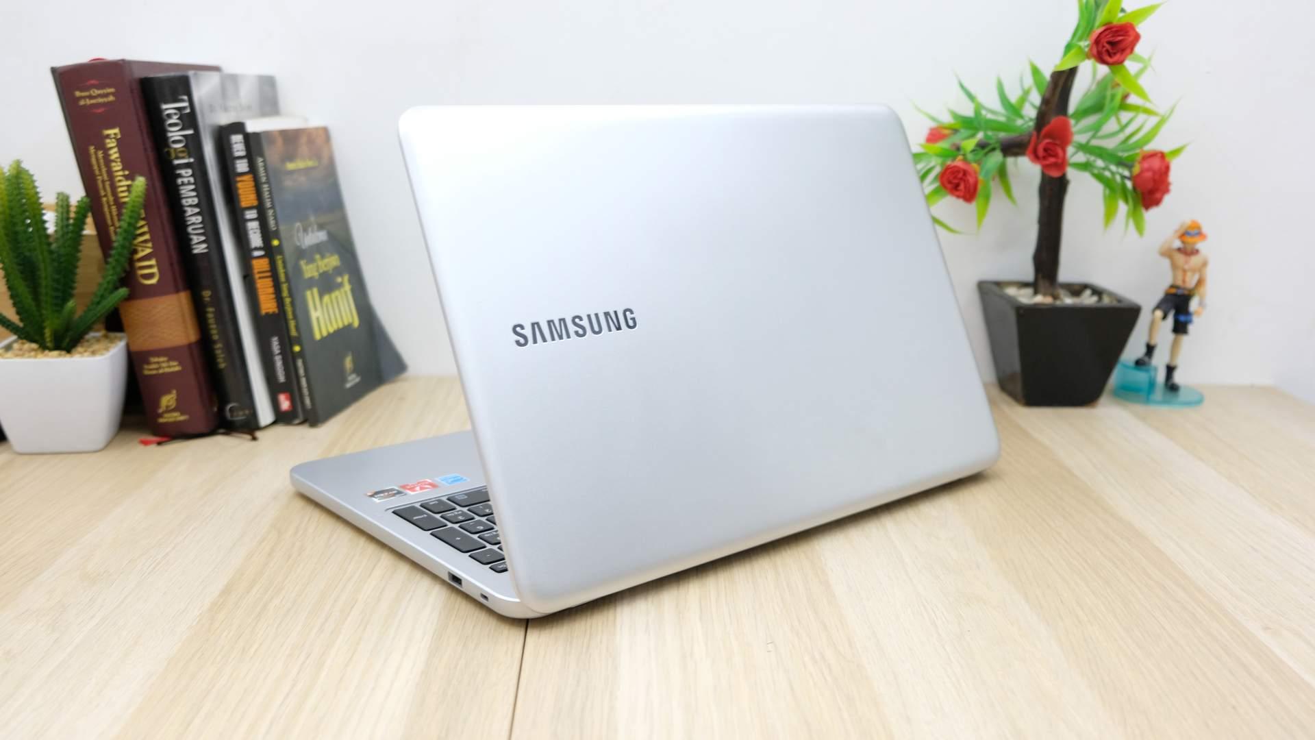 Parte traseira de notebook Samsung aberta em mesa de madeira com decoração de livros e plantas ao fundo