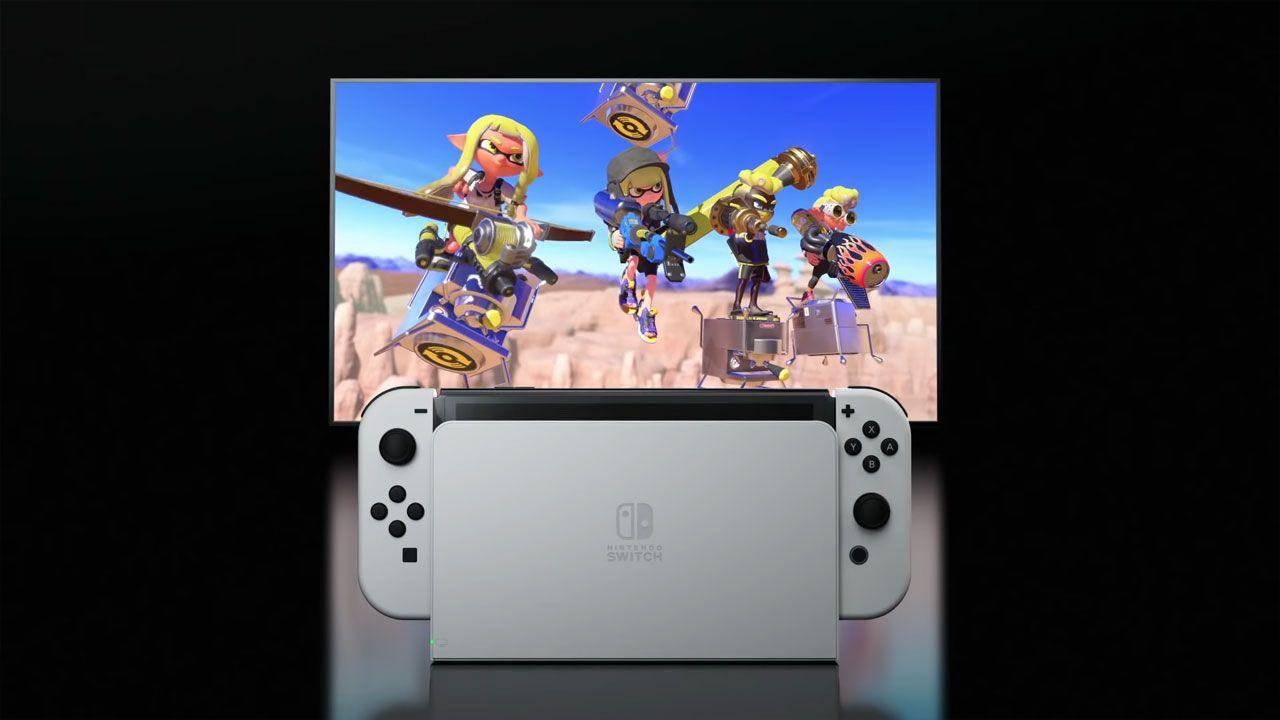 Nintendo Switch OLED na estrutura que o conecta à TV em primeiro plano, com televisão rodando os jogos em segundo plano.