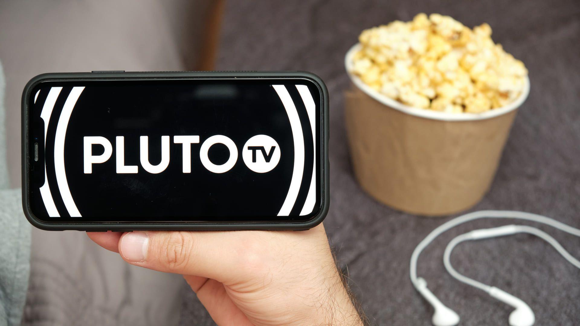 Mão de homem segurando smartphone com Pluto TV escrito na tela. Ao fundo, fones de ouvido e balde de pipoca