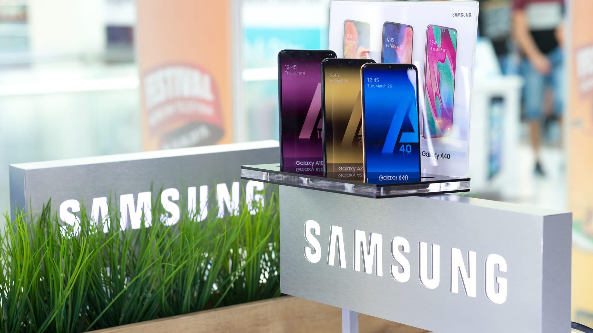Três celulares samsung dispostos em prateleira acima do símbolo da marca