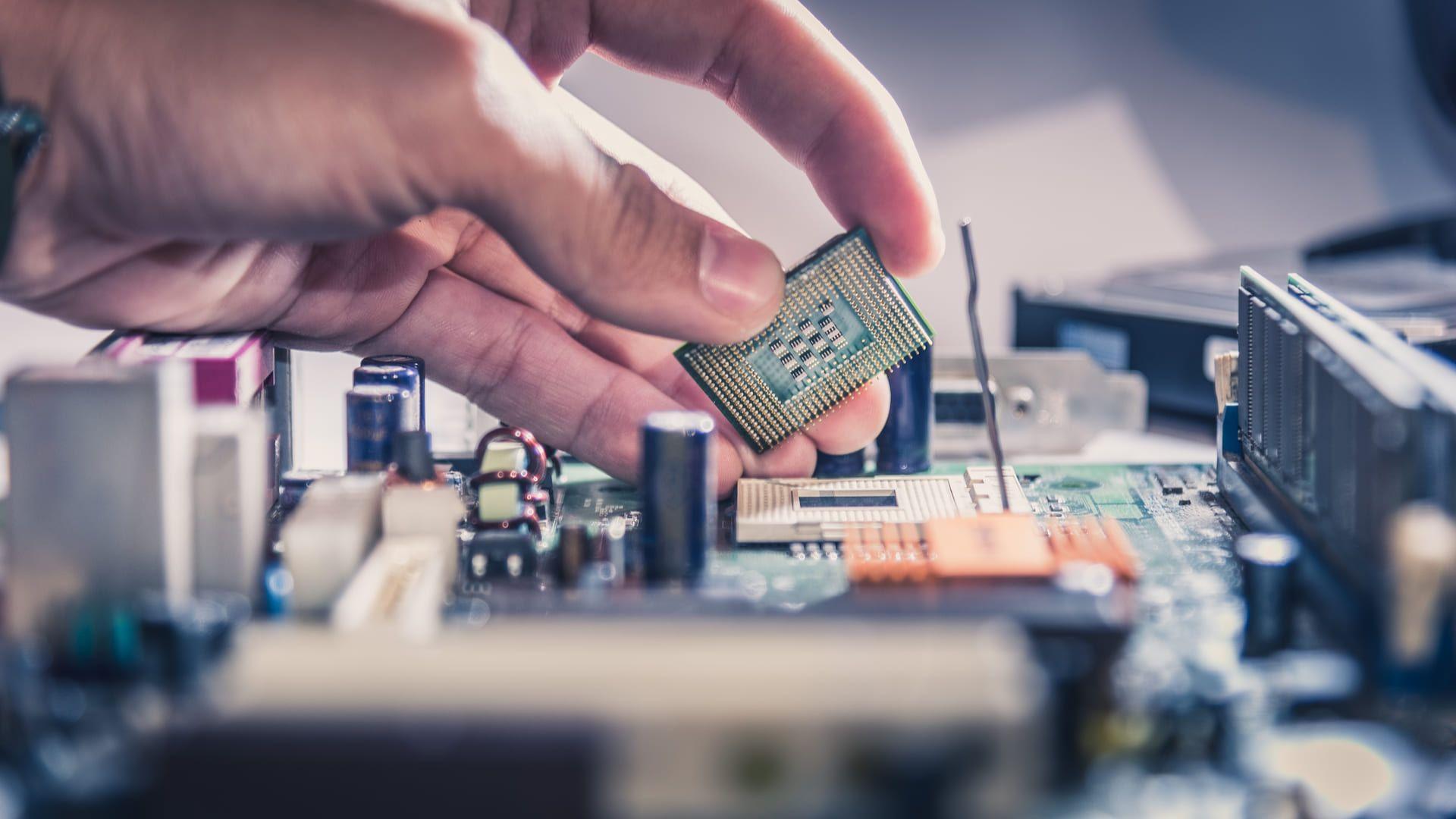 Foto mostra mão colocando chip do processador