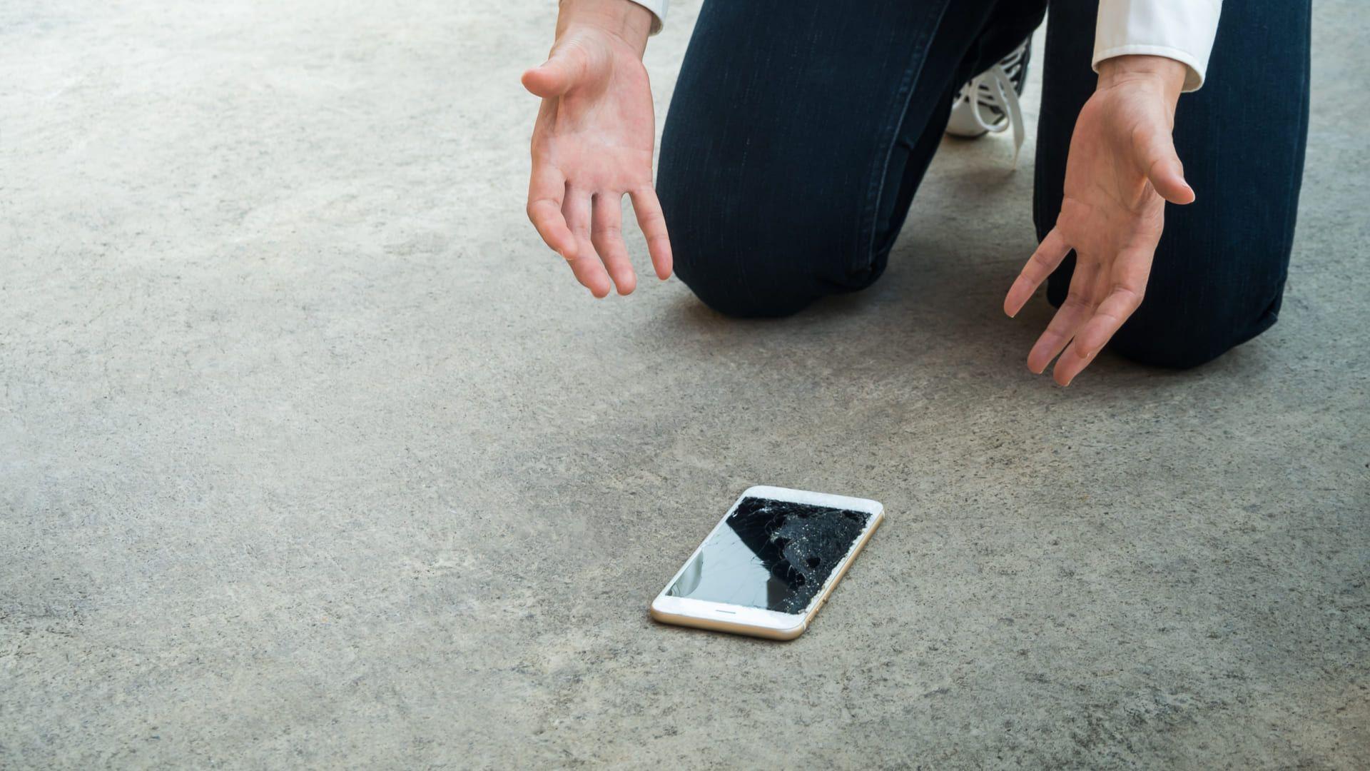 Foto mostra celular caído no chão com a tela trincada