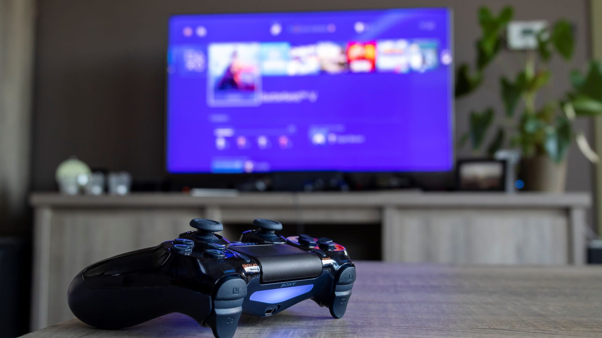 Controle de PS4 preto sobre mesa, com TV mostrando tela inicial do PS4 em TV mostrada em fundo desfocado