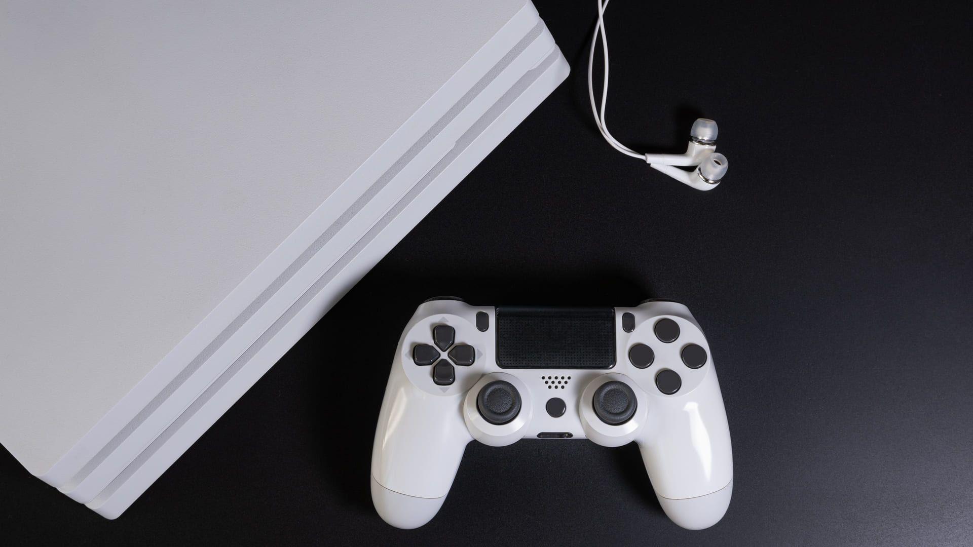 PS4 e controle branco sobre mesa preta, com fones de ouvido ao lado
