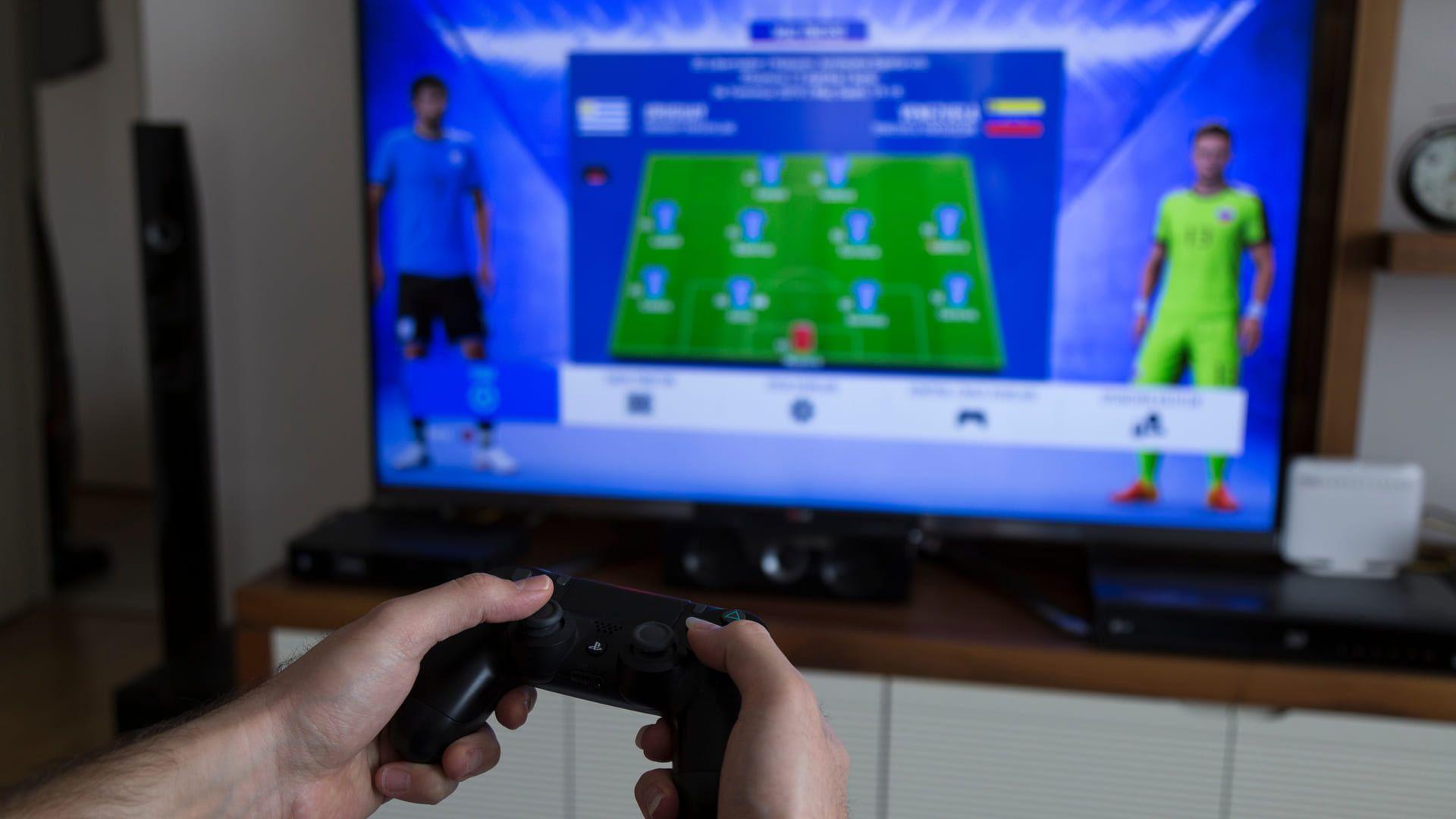 Homem jogando com controle de PS4 com jogo de futebol sendo exibido em TV no fundo desfocado da tela