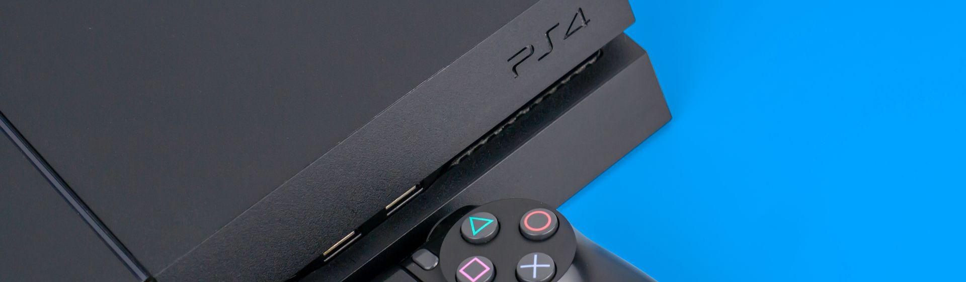 PS4 e controle DualShock 4 pretos sobre fundo azul