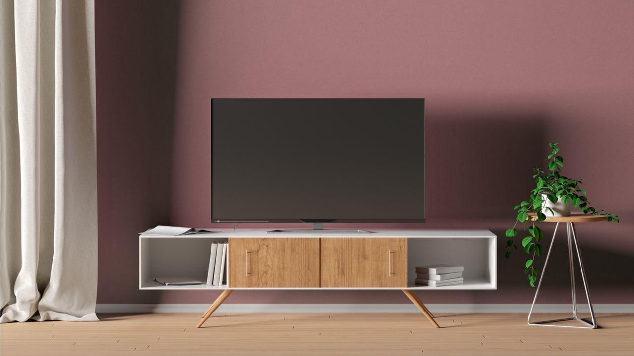 TV desligada sobre rack branco com detalhes em madeira. A parede atrás do rack é rosa e, do lado, há uma mesinha com plantas