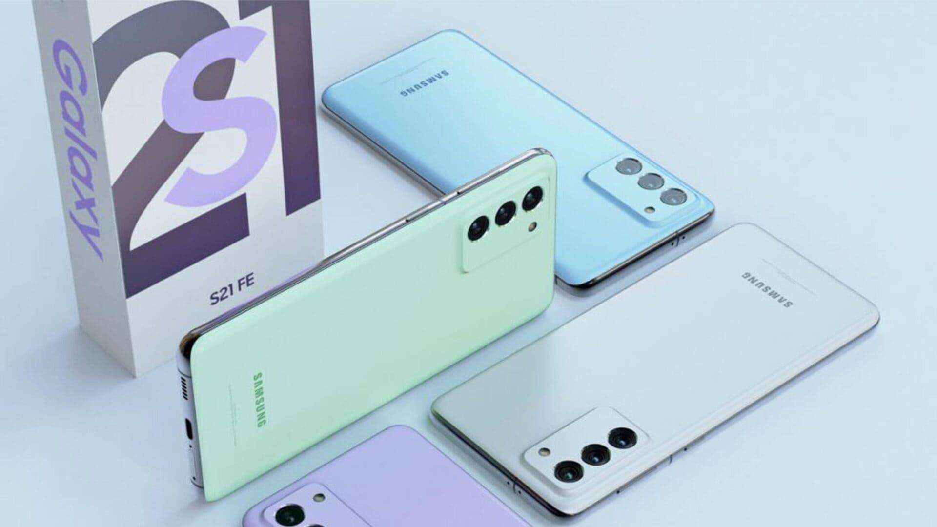 Quatro celulares Galaxy S21 FE de cores diferentes e caixa branca em fundo azul claro