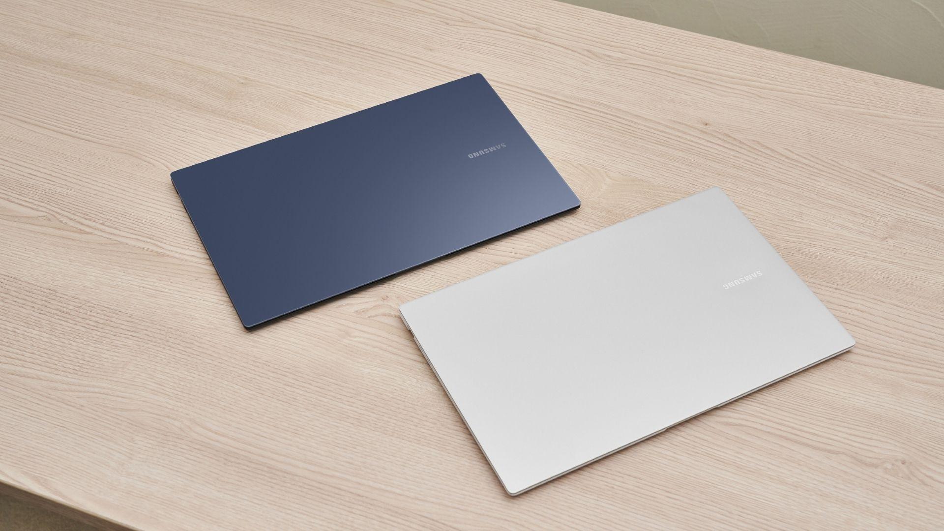 Um notebook cinza escuro e um notebook cinza claro deitados na diagonal