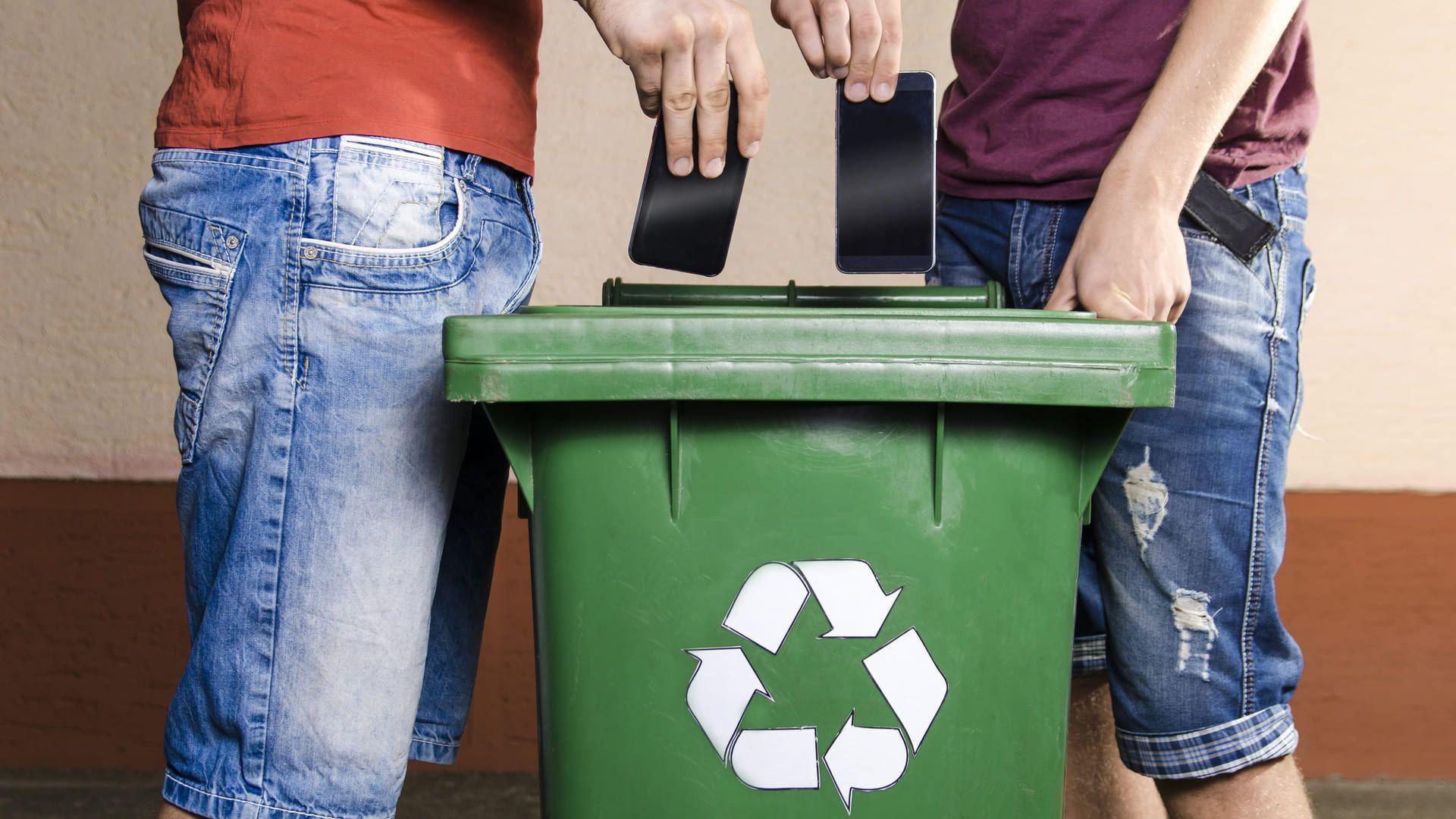 Duas pessoas colocando celulares em uma lixeira de reciclagem