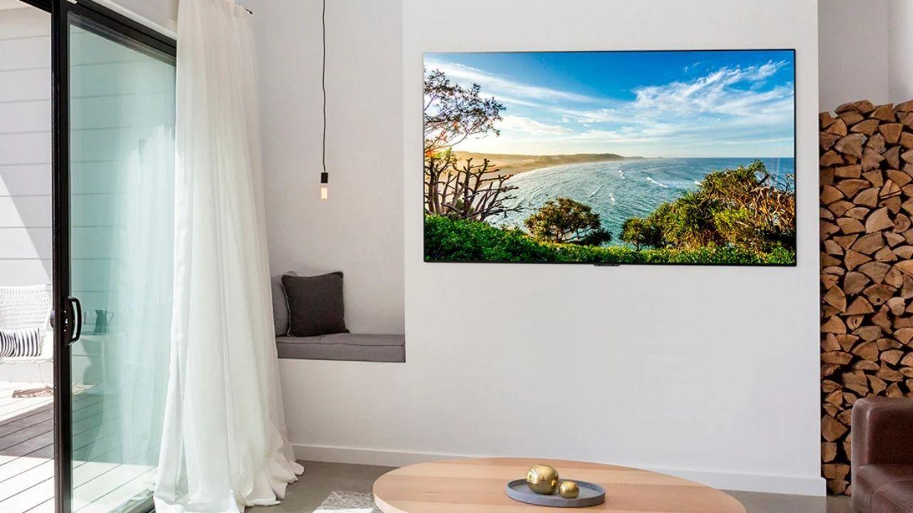 TV LG OLED em parede branca de sala de estar, com mesa de centro redonda de madeira, cortina branca e uma luminária pendurada