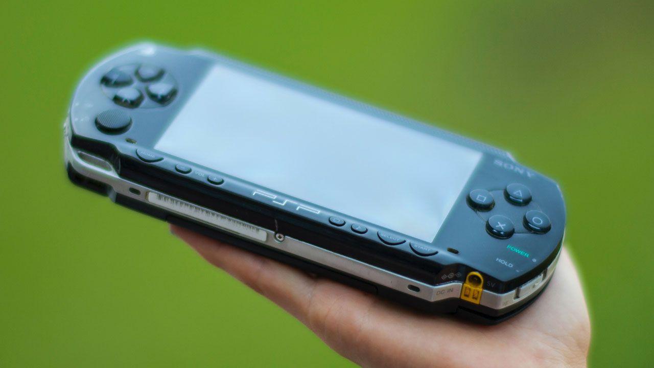 Mão segurando um PSP preto