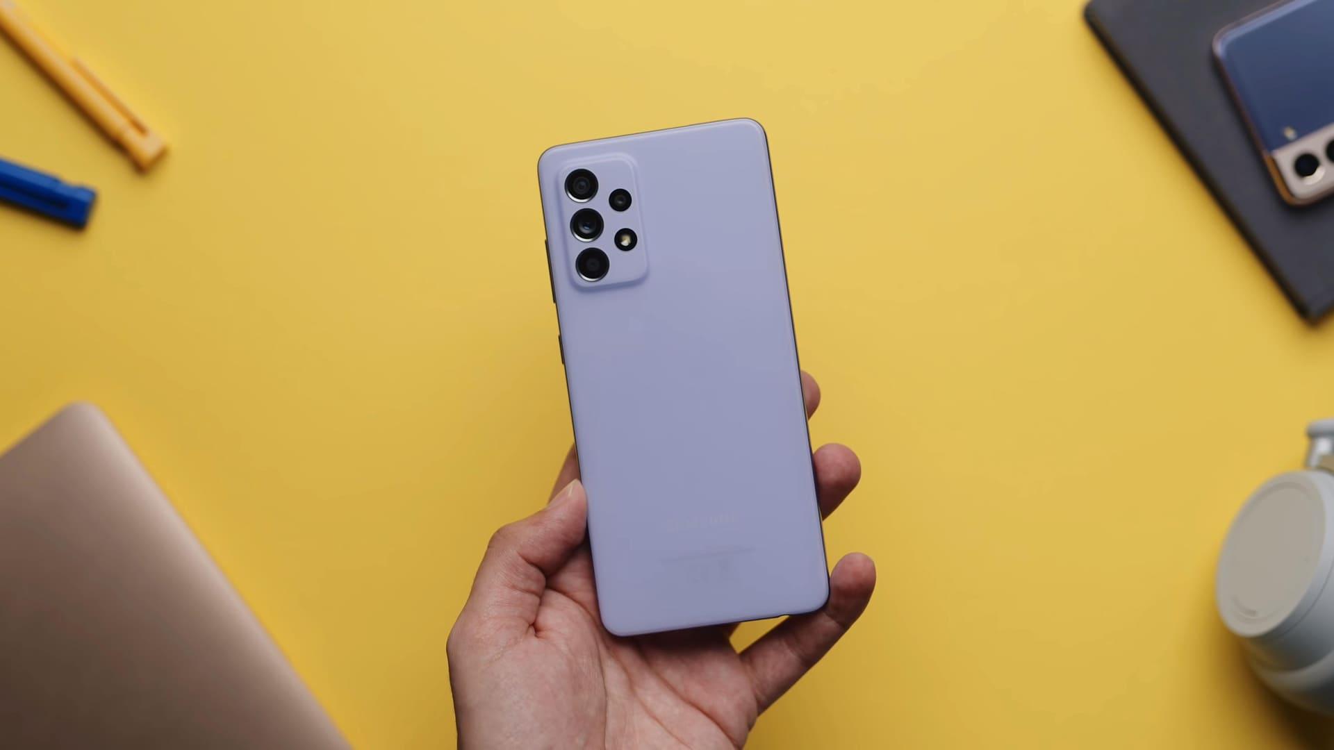 Mão segurando celular A52 e exibindo parte traseira do smartphone