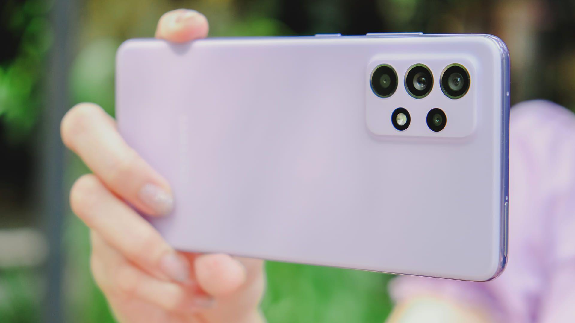 Imagem mostra mão exibindo parte traseira do A52 5G, com seu conjunto quádruplo de câmeras