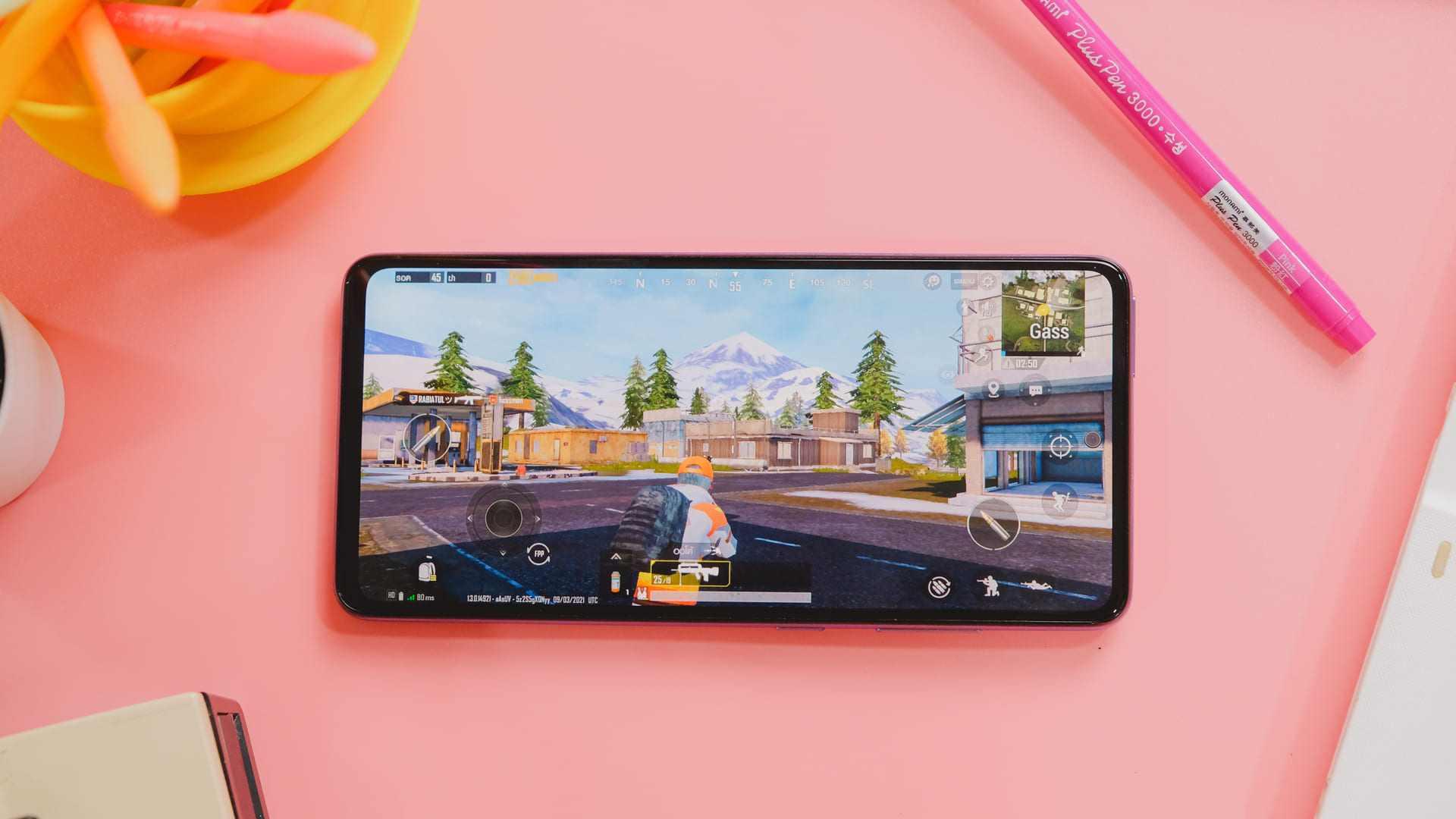 Celular A52 5G com parte frontal voltada para cima exibindo um jogo