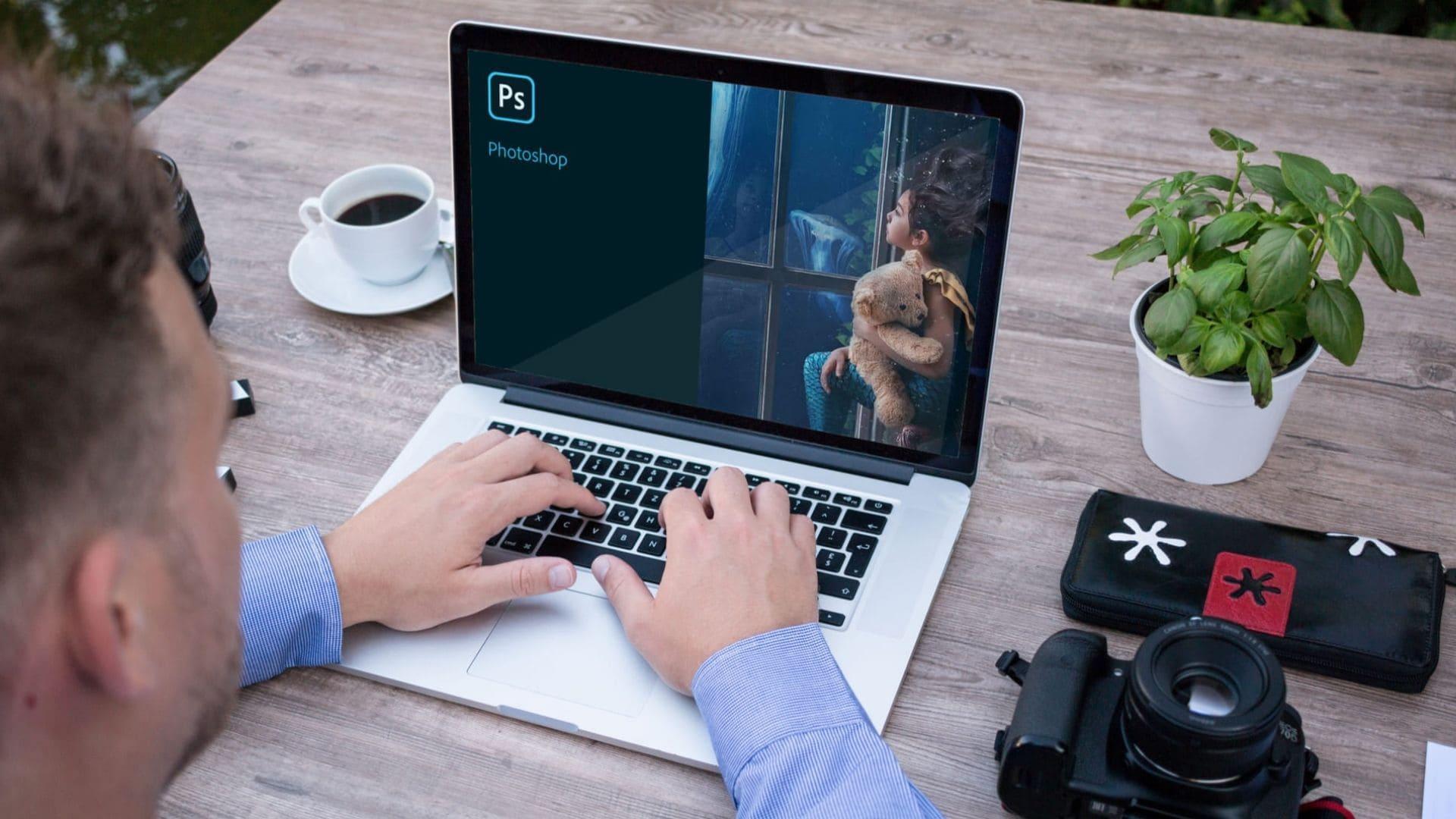 Homem usando Adobe Photoshop no notebook em cima de mesa de madeira