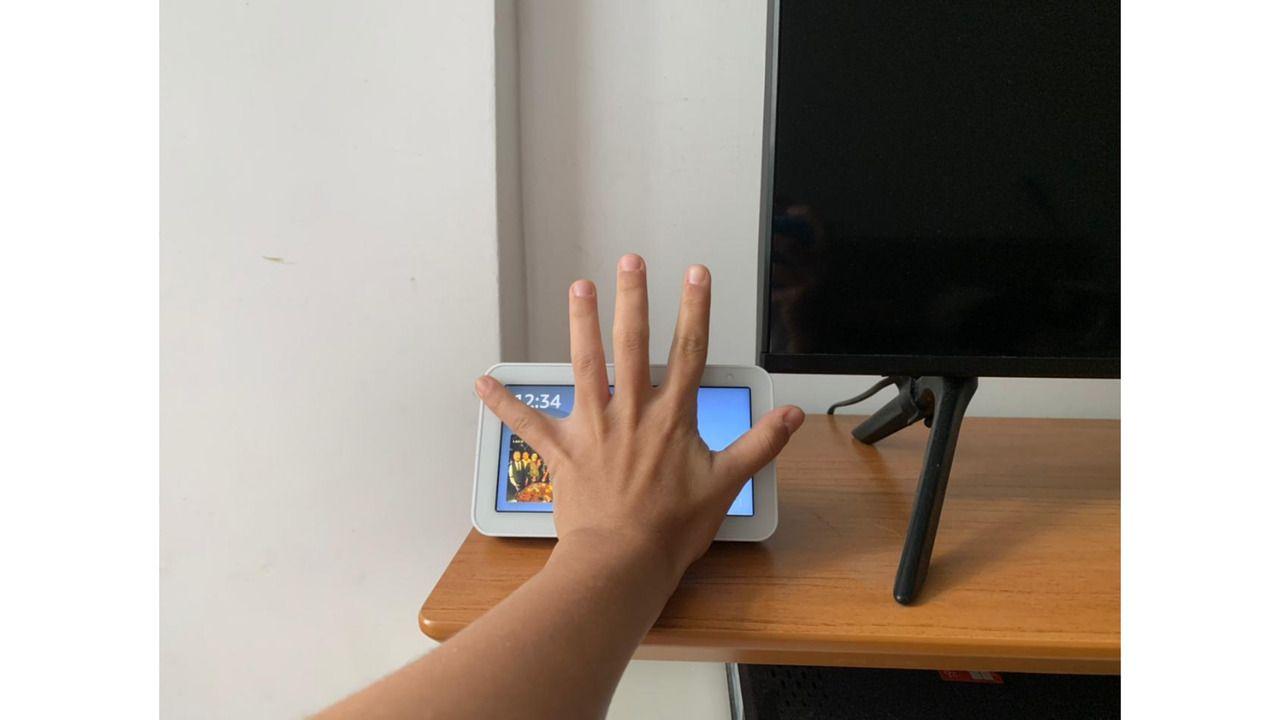 Alexa Echo Show 5 em comparação com uma mão feminina adulta.