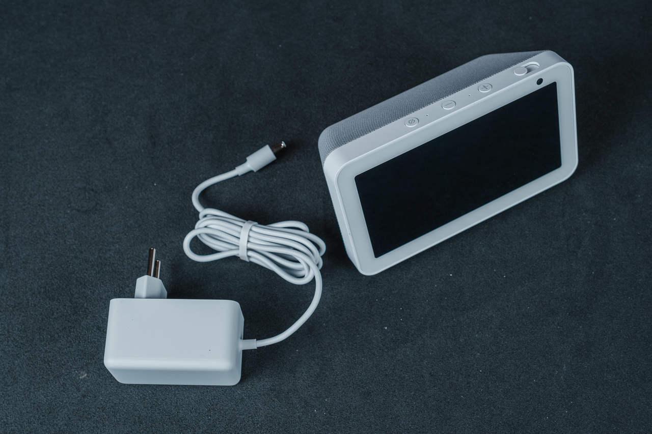 Echo Show 5 ao lado do cabo de energia do produto, ambos apoiados em superfície cinza.
