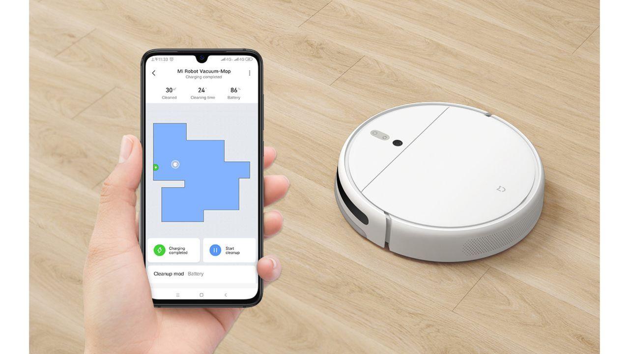 Mi Robot Vacuum MOP em chão de madeira com mão segurando um celular aberto no aplicativo Mi Home.
