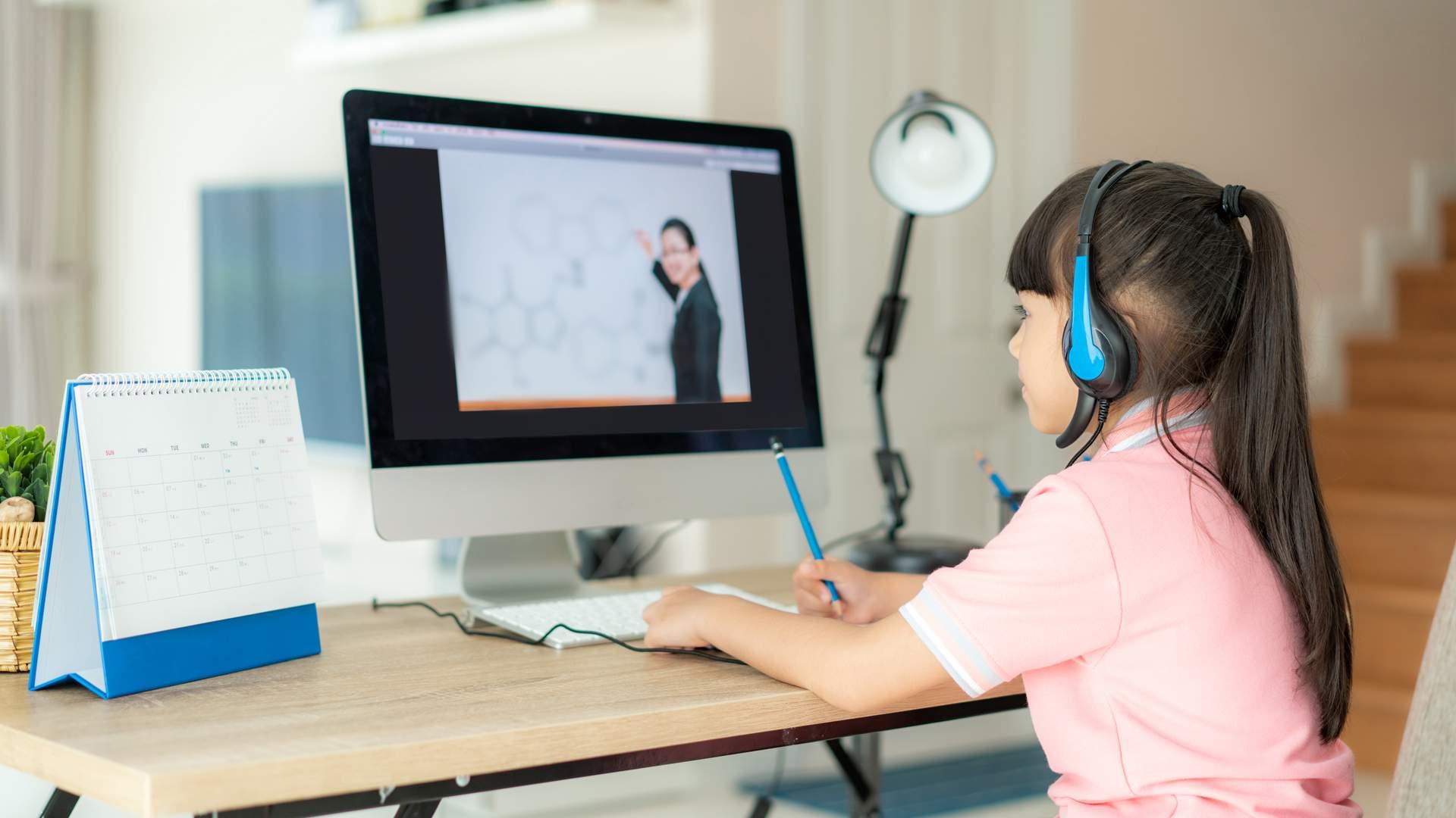 Menina assistindo videoaula em monitor sobre mesa de madeira