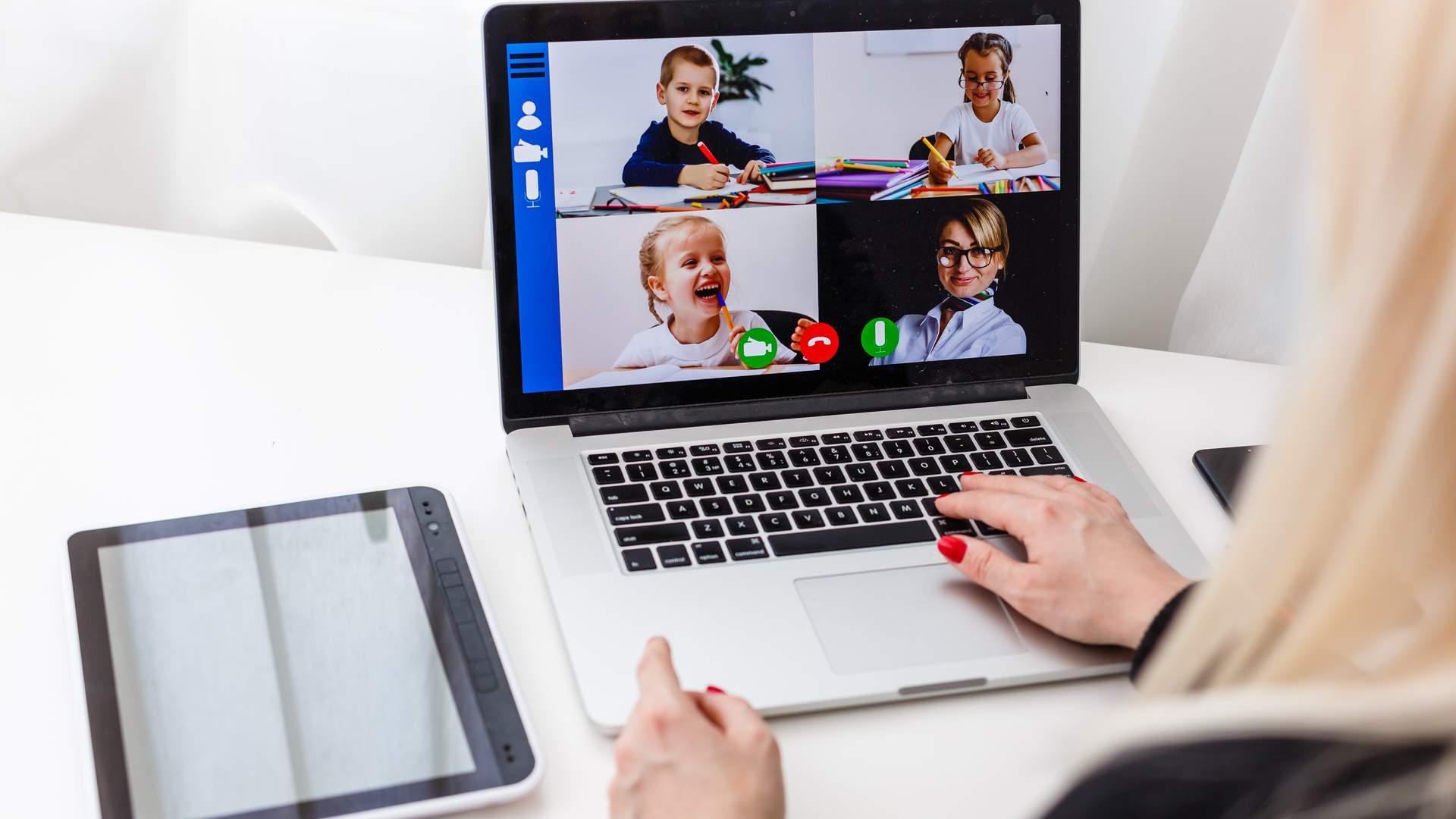Notebook exibindo aula online na tela sobre mesa branca, com tablet preto ao lado