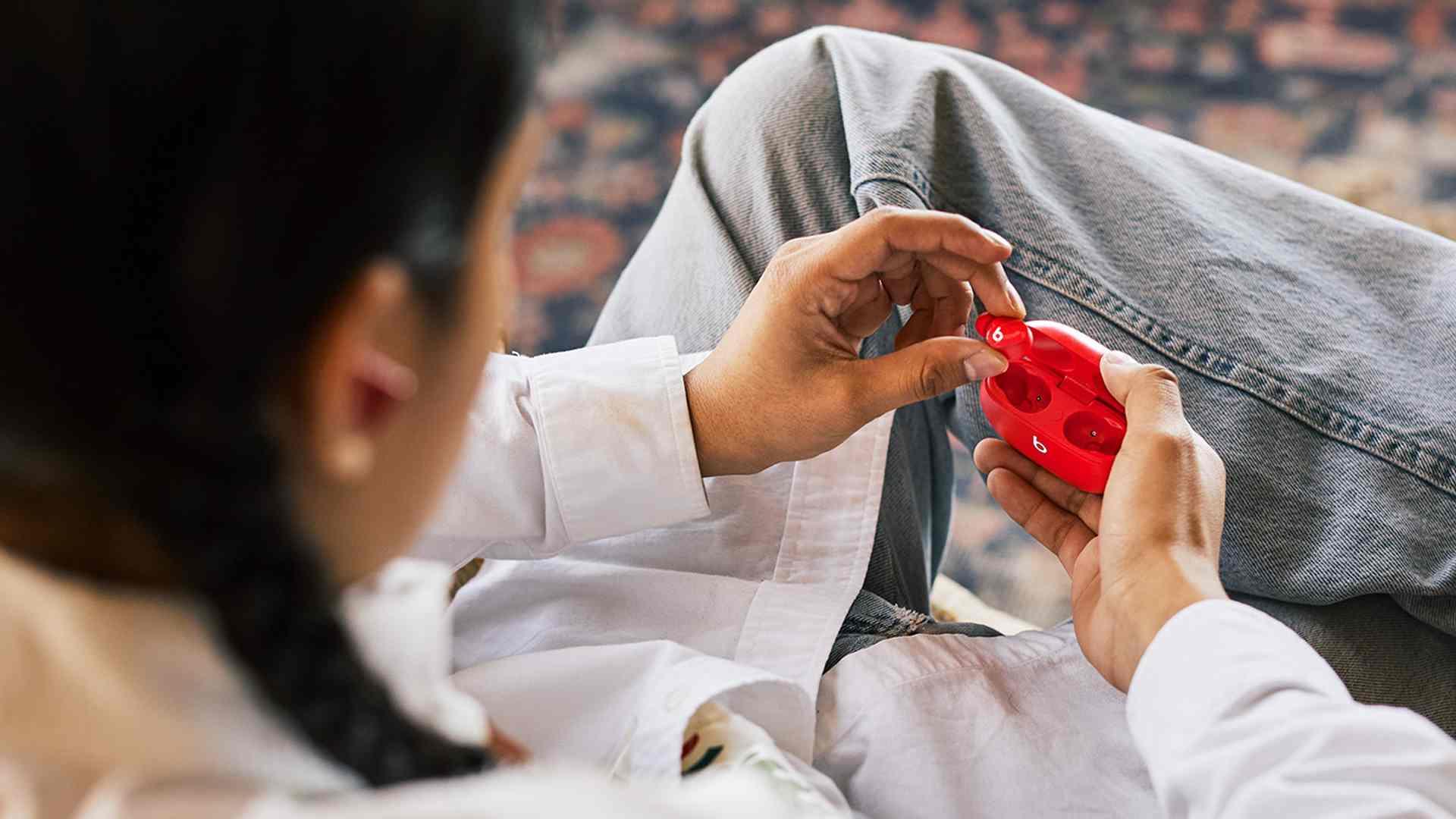 Imagem mostra pessoa tirando um fone Beats Studio Buds do estojo