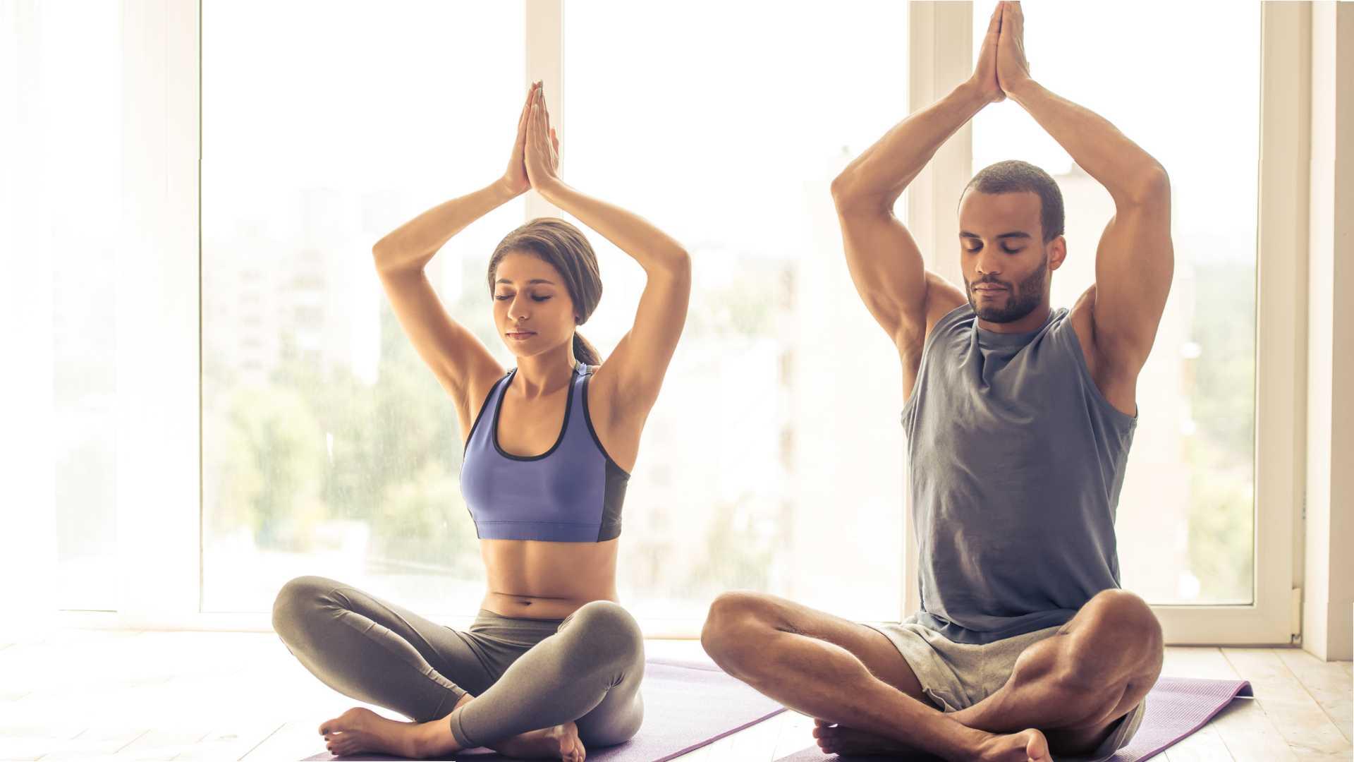 Casal fazendo yoga em casa