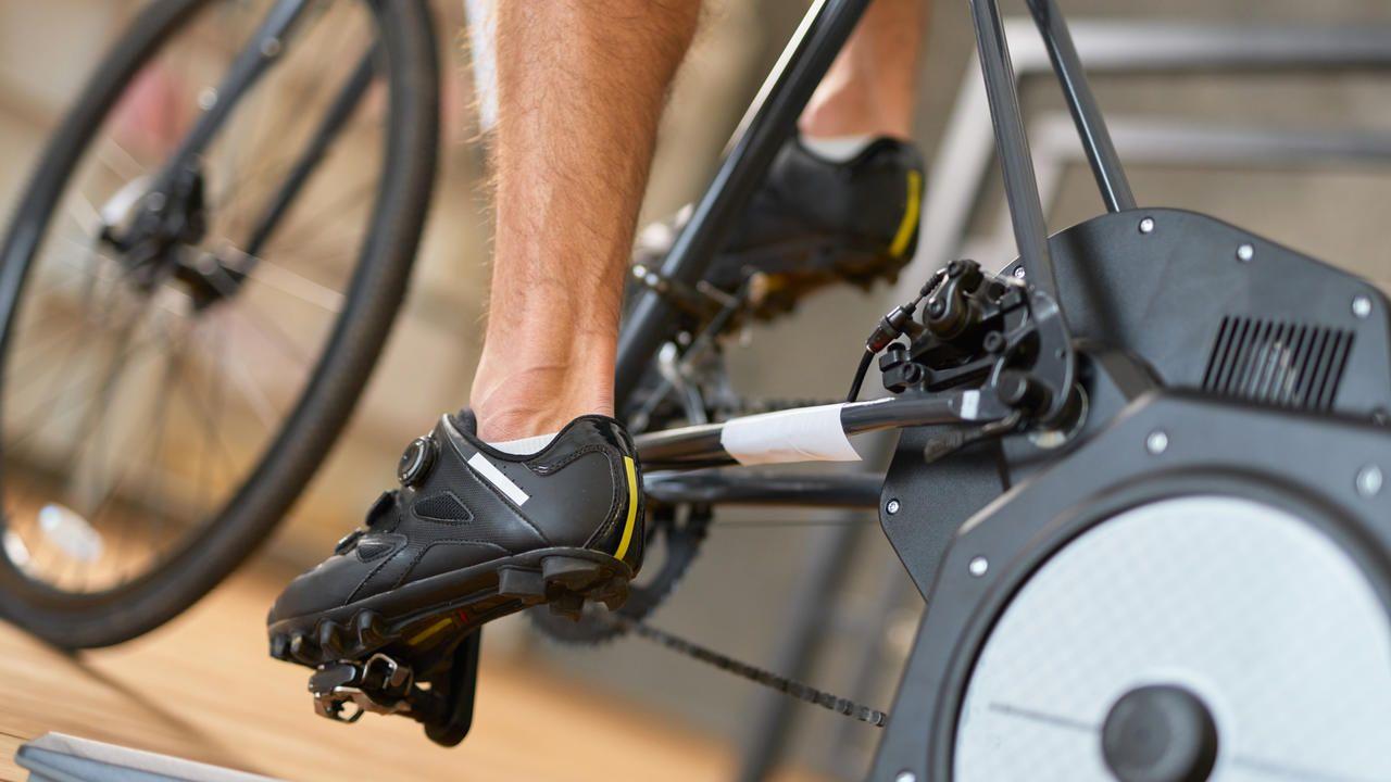 Homem treinando em bicicleta ergométrica usando sapatilhas pretas