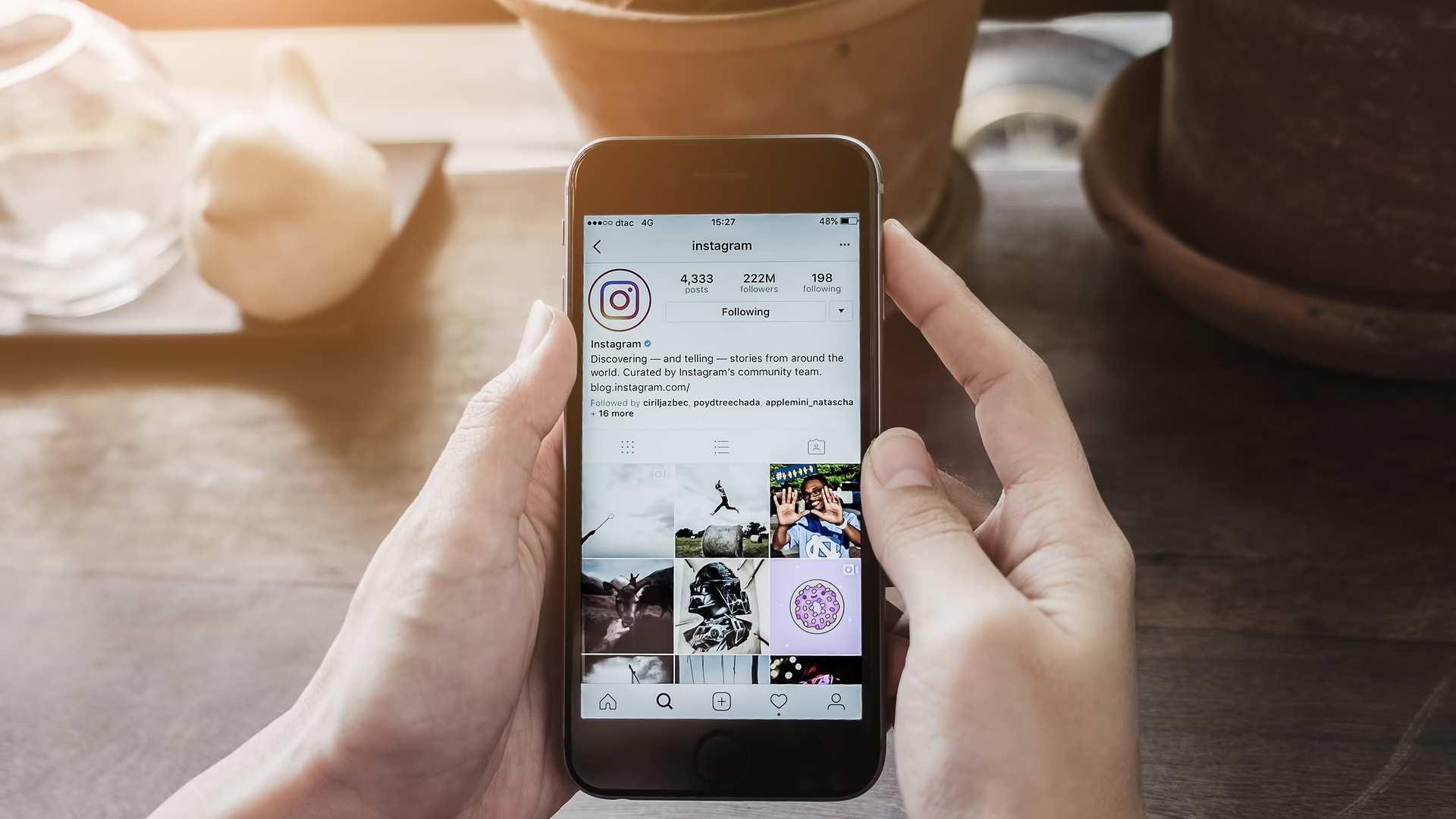 Pessoa lendo a biografia para Instagram no celular em cima de uma mesa com vaso e copos