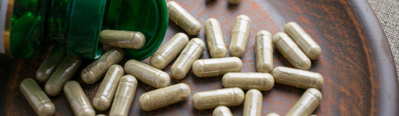 Pílulas marrons em prato de madeira