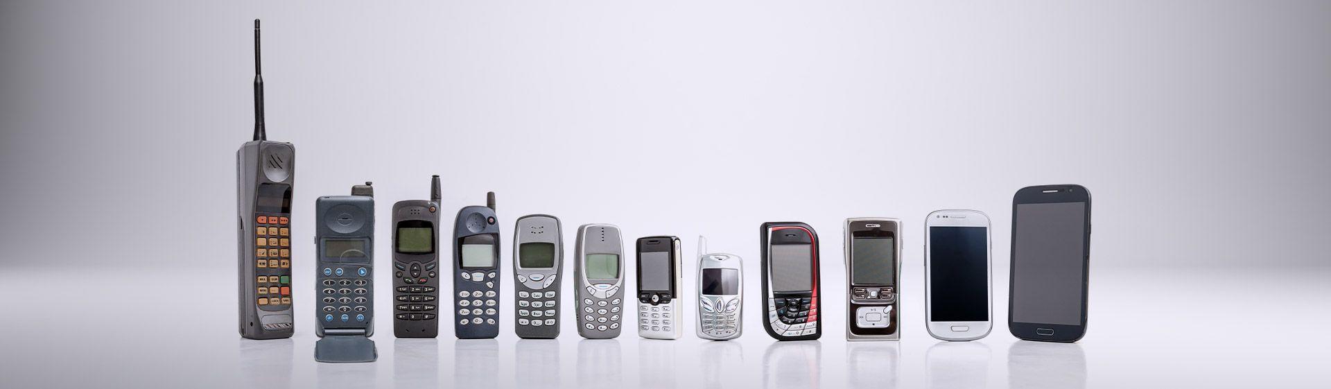 12 celulares antigos lado a lado em fundo acinzentado